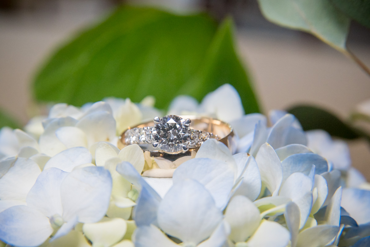 close up photos of bride and grooms wedding rings with flowers