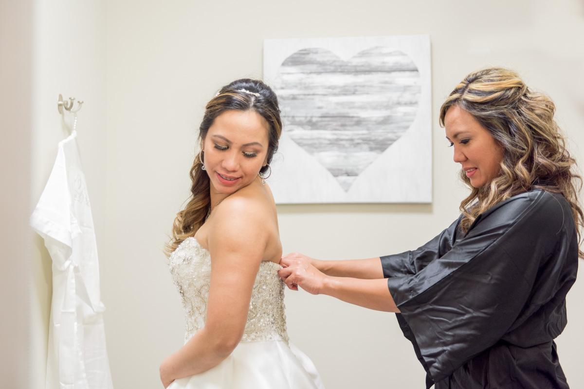 bride and sister helping get into wedding dress